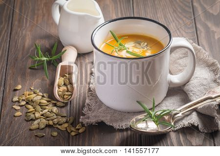 Roasted pumpkin soup with cream and pumpkin seeds on wooden background.