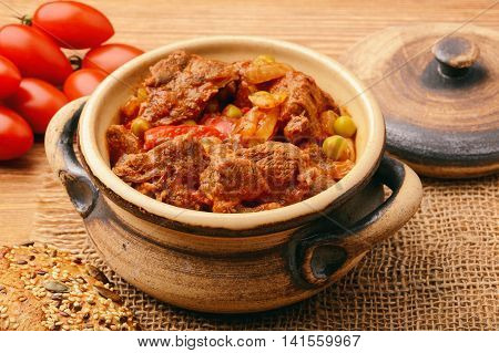Venison goulash on brown wooden background .