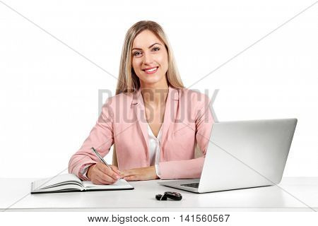 Seller woman at table with laptop and car key isolated on white