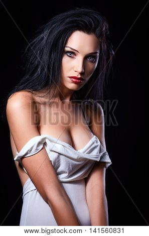 Studio fashion shot: dramatic portrait of a sexy beautiful young woman in white dress