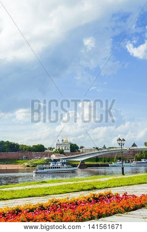 VELIKY NOVGOROD RUSSIA - AUGUST 5 2016. Novgorod Kremlin with footbridge and pleasure boat floating the Volkhov river in summer sunny day - architecture landscape. Selective focus at the Kremlin