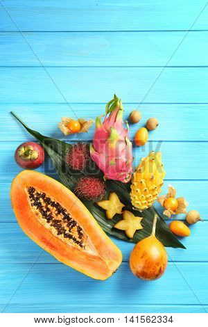 Juicy exotic fruits on blue wooden background