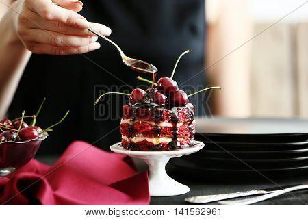 Female hand decorating cherry cake on stand