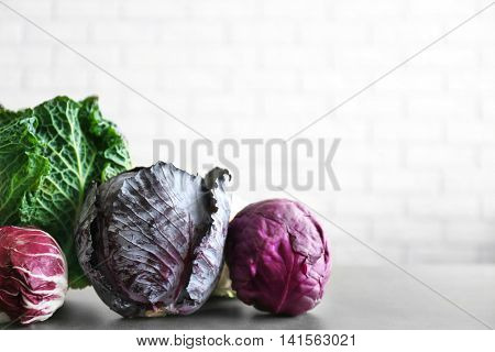 Different kinds of cabbage on brick wall background