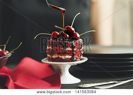 Decorating cherry cake on stand