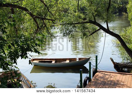 Little landing stage and the boat in a small Russian River