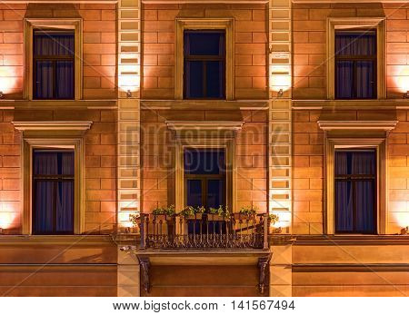 Several windows in a row and balcony on night illuminated facade of Angleterre Hotel front view St. Petersburg Russia