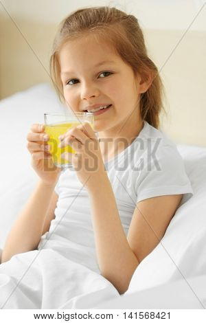Cute girl with juice in white bed