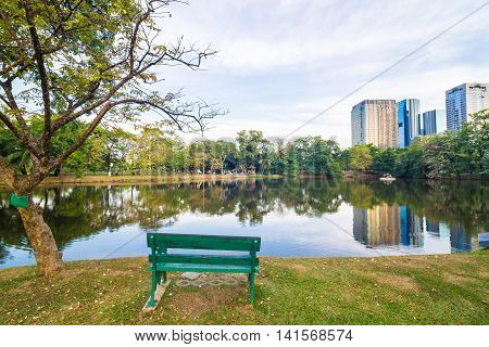 Park Bench Near Pond In A Quiet City On  Sunny Day