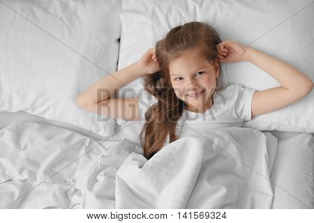 Cute girl in white bed