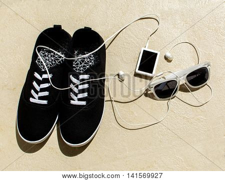 Black sneakers, white walkman with headphones and white sunglasses. Top view