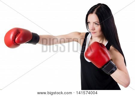 Young beautiful brunette girl with long hair in red boxing gloves is training a kick. Isolated on white background in studio