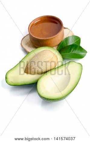 fresh avocado with avocado oil in the wooden bowl isolated on white background