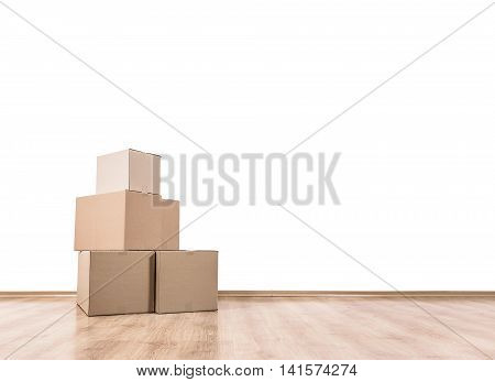 Empty room with a white wall and moving boxes on the floor.