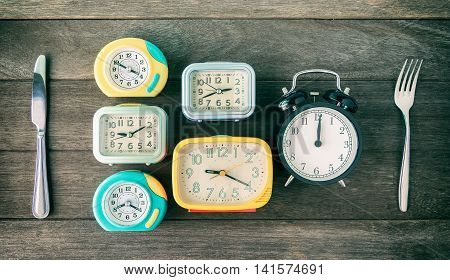 Meal time Time to eat concept. Clocks with spoon and folk on wood table. Vintage color filtered.