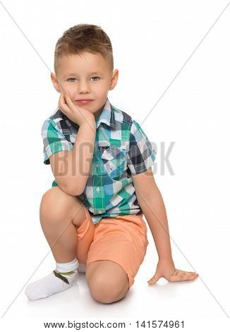 Nicely combed little boy in a plaid shirt and pink shorts is kneeling on the floor, put his head on his hand