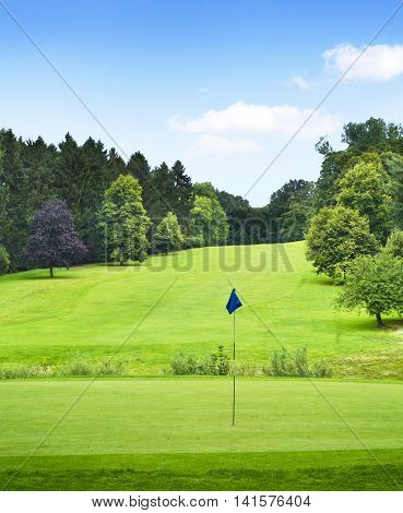 Idyllic golf course with forest and putting green with flag. Summer landscape, park.