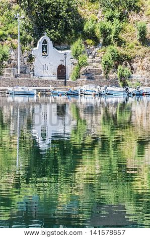 A church reflected in the water at the seaside resort town of Agios Nikolaos located on the north-east side of Crete Greece.