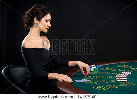 sexy woman with poker cards and chips. Female player in a beautiful black dress. girl sitting at the poker table and bets