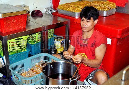 Bangkok Thailand - December 16 2011: Thai worker preparing bags of Satay oil at the Or Tor Kor Fresh Produce & Food Market