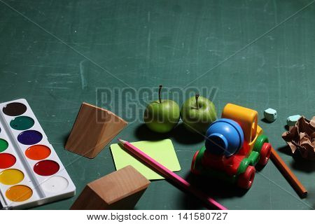 School stationery colorful paints pencils yellow stick paper wooden blocks green apples car toy piece of chalk laying on blackboard copy space