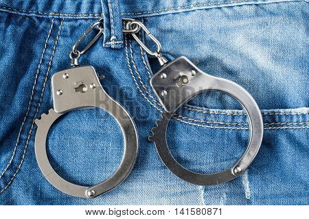 The handcuffs hanging on a belt of blue jeans