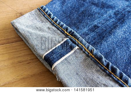 Fold Legs Vintage Jeans  On Wooden Table.