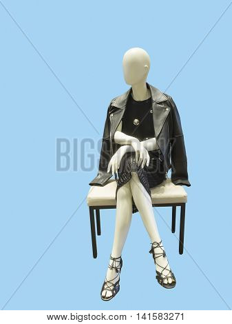 Sitting female mannequin wearing black dress and leather jacket against blue background. No brand names or copyright objects.