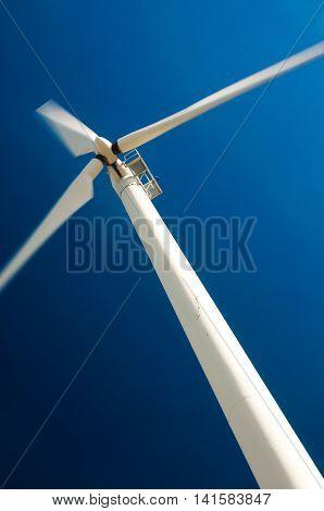 Wind turbine in motion against blue sky - clean energy