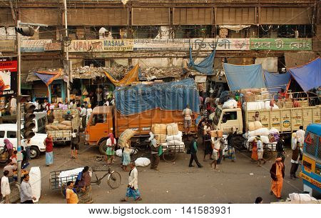 KOLKATA, INDIA - JAN 17, 2013: Crowd of workers and trucks in poor working area of indian city on January 17, 2013 in India. Kolkata has a density of 814.80 vehicles per km road length
