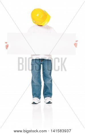 Full length portrait of little foreman or construction worker in yellow helmet, presenting blank board - isolated. Boy wearing protect helmet posing on white background.