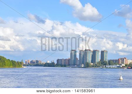View of Neva river and microdistrict Ribatskoe on the outskirts of St. Petersburg at sunny summer day Russia.