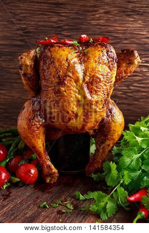 Gourmet Roast Whole organic chicken on cider Can With Asparagus, glazed Cherry Tomatoes, Herb and Spices, Served on Top of a Wooden Table