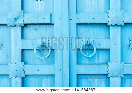 Metal blue aged textured door with rings door handles and metal details in form of stylized flowers. Metal architecture background.