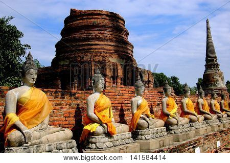 Ayutthaya Thailand - December 28 2005: Rows of seated Buddha statues draped in orange and saffron robes in the cloister gallery ruins at Wat Yai Chai Mongkon