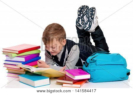 Young male student is lying on the floor, reading a book. Isolated on a white background. Happy schoolboy with backpack and books - back to school concept.