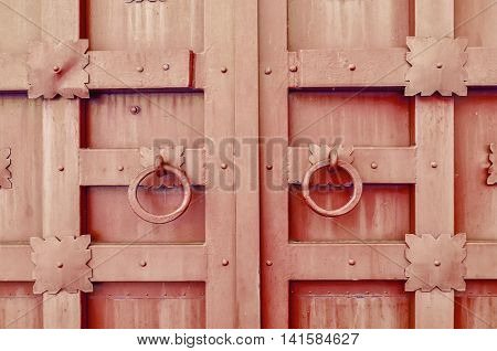 Metal brown aged textured door with rings door handles and metal details in form of stylized flowers. Metal architecture background.