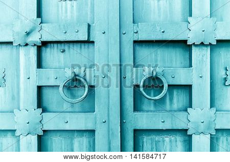Metal dark turquoise aged textured door with rings door handles and metal details in form of stylized flowers. Metal architecture background.