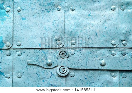 Metal light blue surface of old hammered metal plates with metal rivets and architectural details on them. Metal bright blue industrial background with peeling paint.
