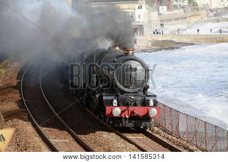 A vintage steam locomotive passes through Dawlish on the famous Brunel railway line