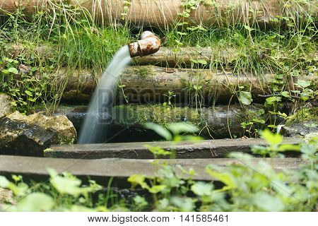 Village scene. Water gushes from a metal pipe.