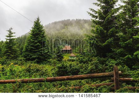Mountain landscape in Carpathians wooden house under hill in rain weather Ukraine
