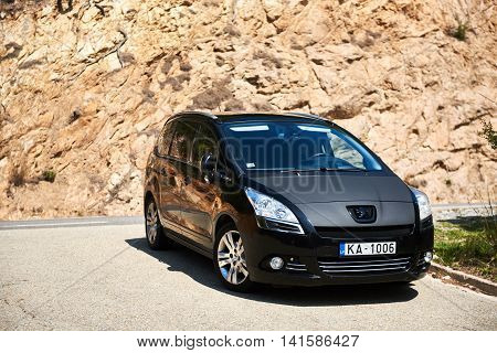 Tossa de Mar Spain - April 7 2016: Black colour Peugeot 5008 stopped on a mountain road in Spain. The Peugeot 5008 is a French car and has been on sale since November 2009