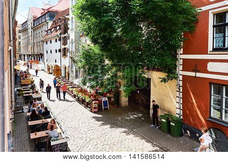 Riga Latvia - July 19 2016: Tourists sitting in a sidewalk cafe in the old town of Riga. Northern Europe. Latvia