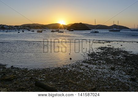 Sunset in the city Buzios with its beach sea islands boats and topography.