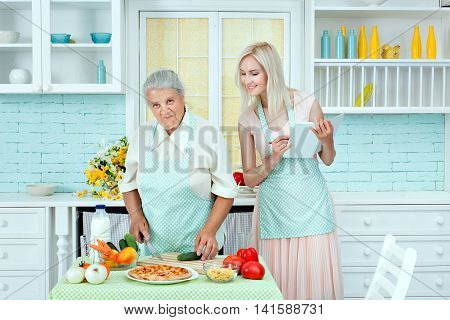 Grandma taught to cook a young girl in the kitchen.