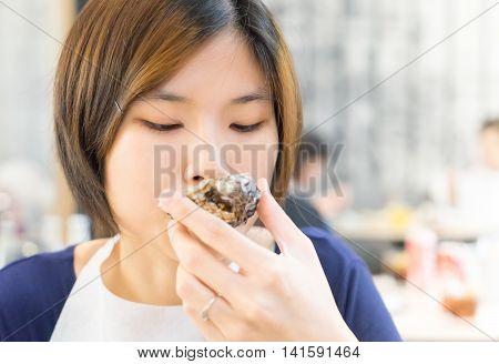 Japanese girl eating fresh oyster in restaurant