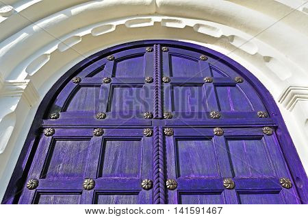 Architecture detailed background - aged wooden door of purple color with metal rivets and upper arch of white stone - vintage architecture background