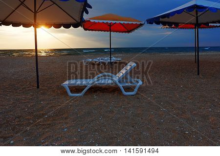 Beach loungers and umbrellas on deserted coast sea at sunset.