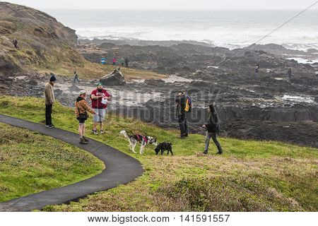 Yachats, USA - Februrary 27, 2016: Hikers with dogs near Thor's well in Cape Perpetua in Oregon